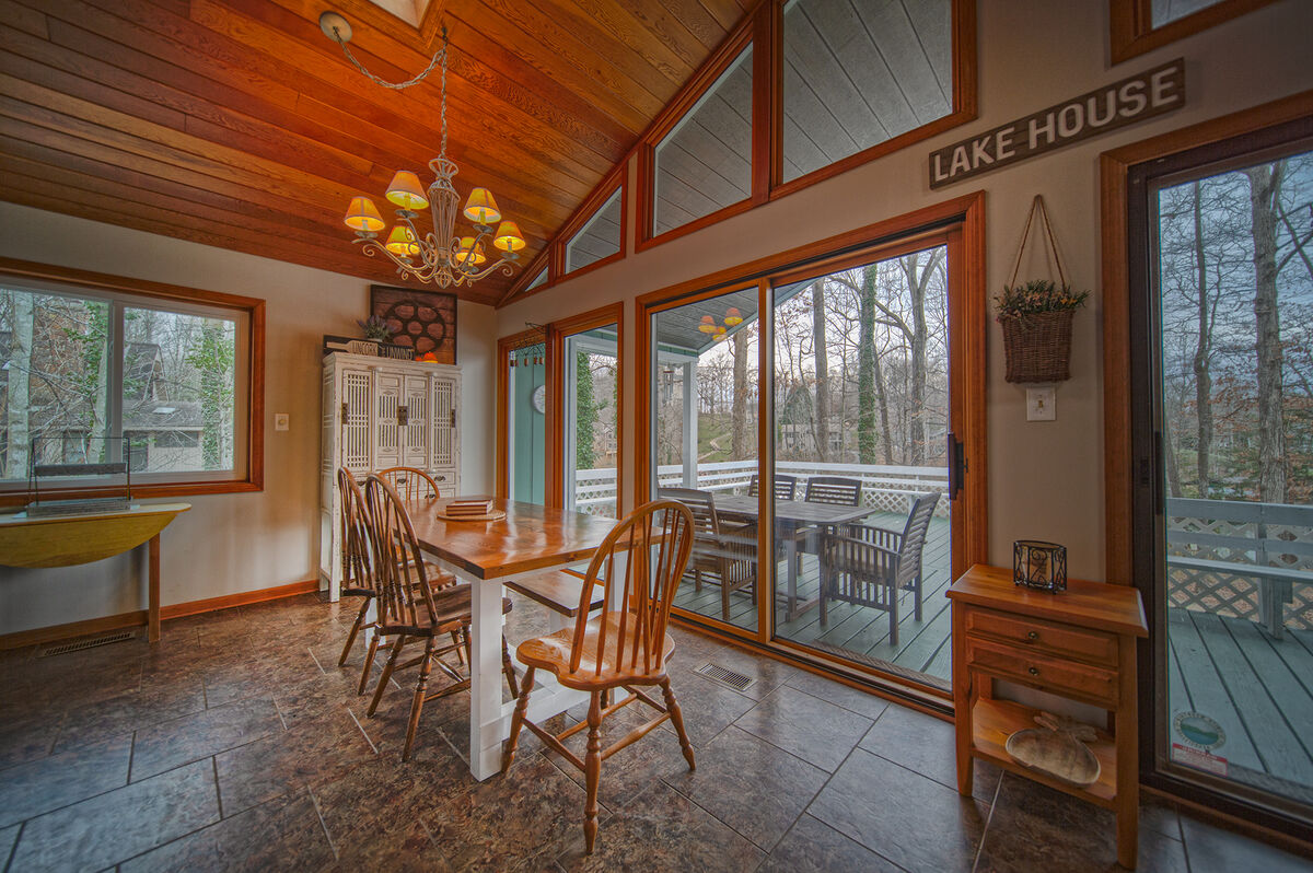 Dining Table, Chairs, Buffet Table, and Windows with Lake View.