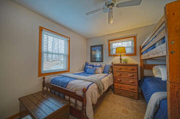 Bedroom with Large Bed, Ceiling Fan, Dresser, and Bunker Bed.