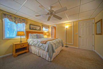Bedroom with Large Bed, Ceiling Fan, Lamps, and Nightstands.