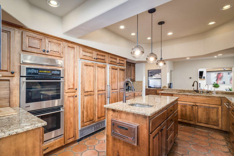 Chef's kitchen with gas stove-top, dual ovens, and granite countertops.