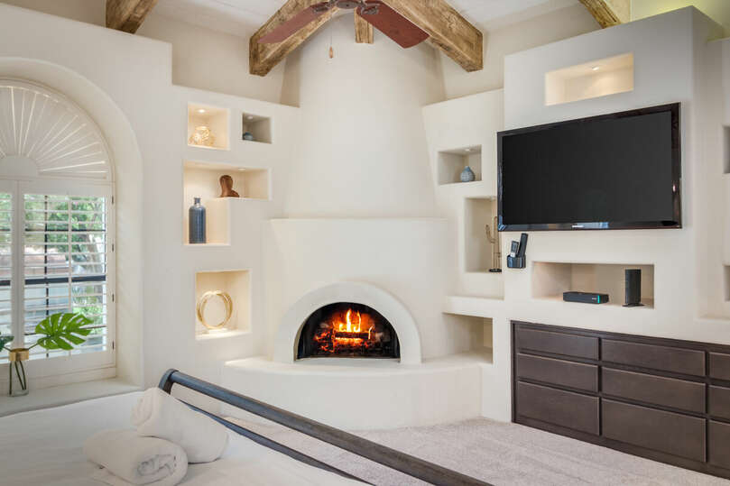 Main bedroom with vaulted ceilings and fireplace.