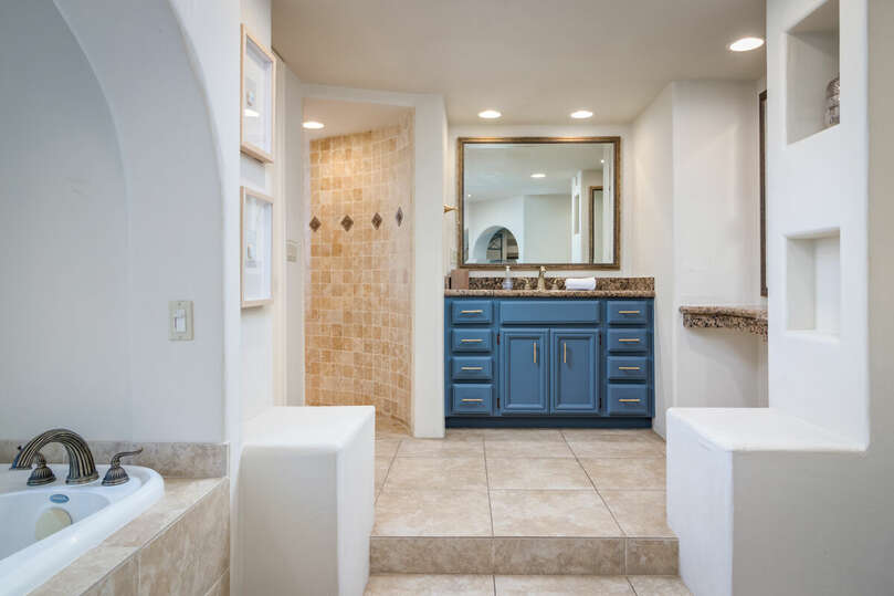 Primary bathroom with dual vanities, separate shower, and bathtub.