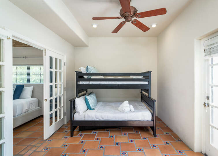 Attached bedroom with bunk beds and a backyard entrance.