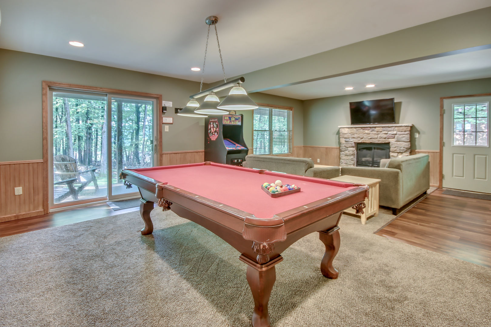 Spacious Game with a Pool Table, Arcade Game, and Large Sofa.