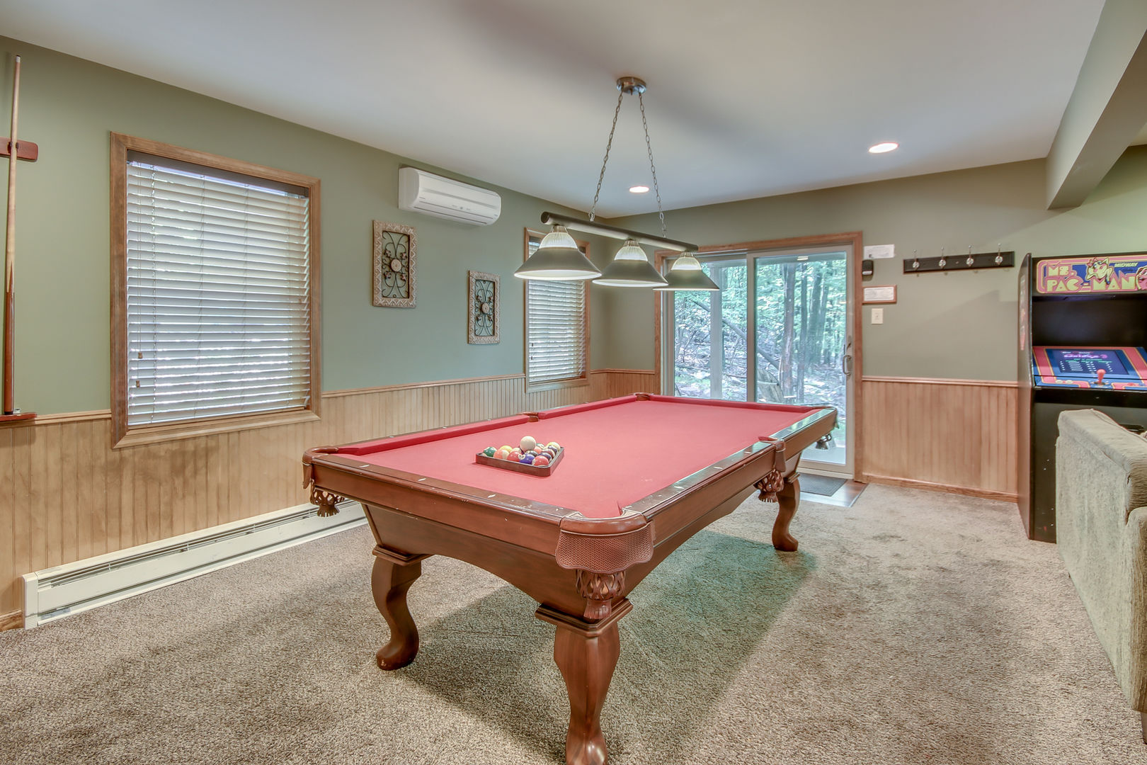 A Game Room Featuring Pool Table and Arcade Game.