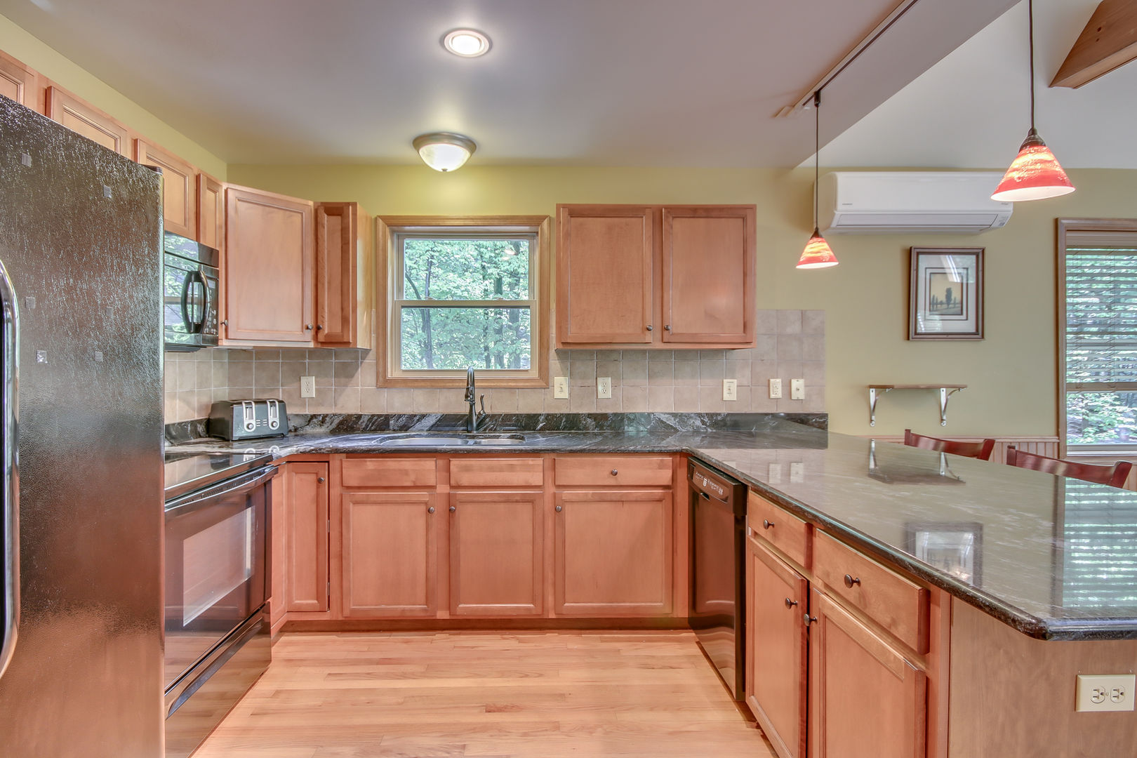 Kitchen Featuring Wooden Cabinets and Sink Facing Backyard.