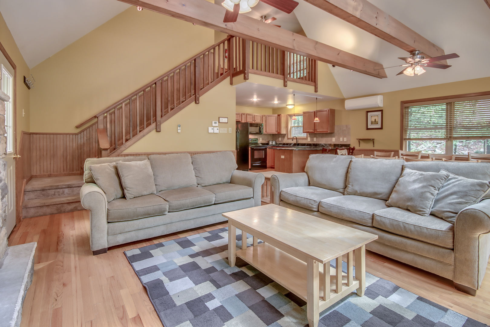 Two Large Sofas and Coffee Table Near Stairs.