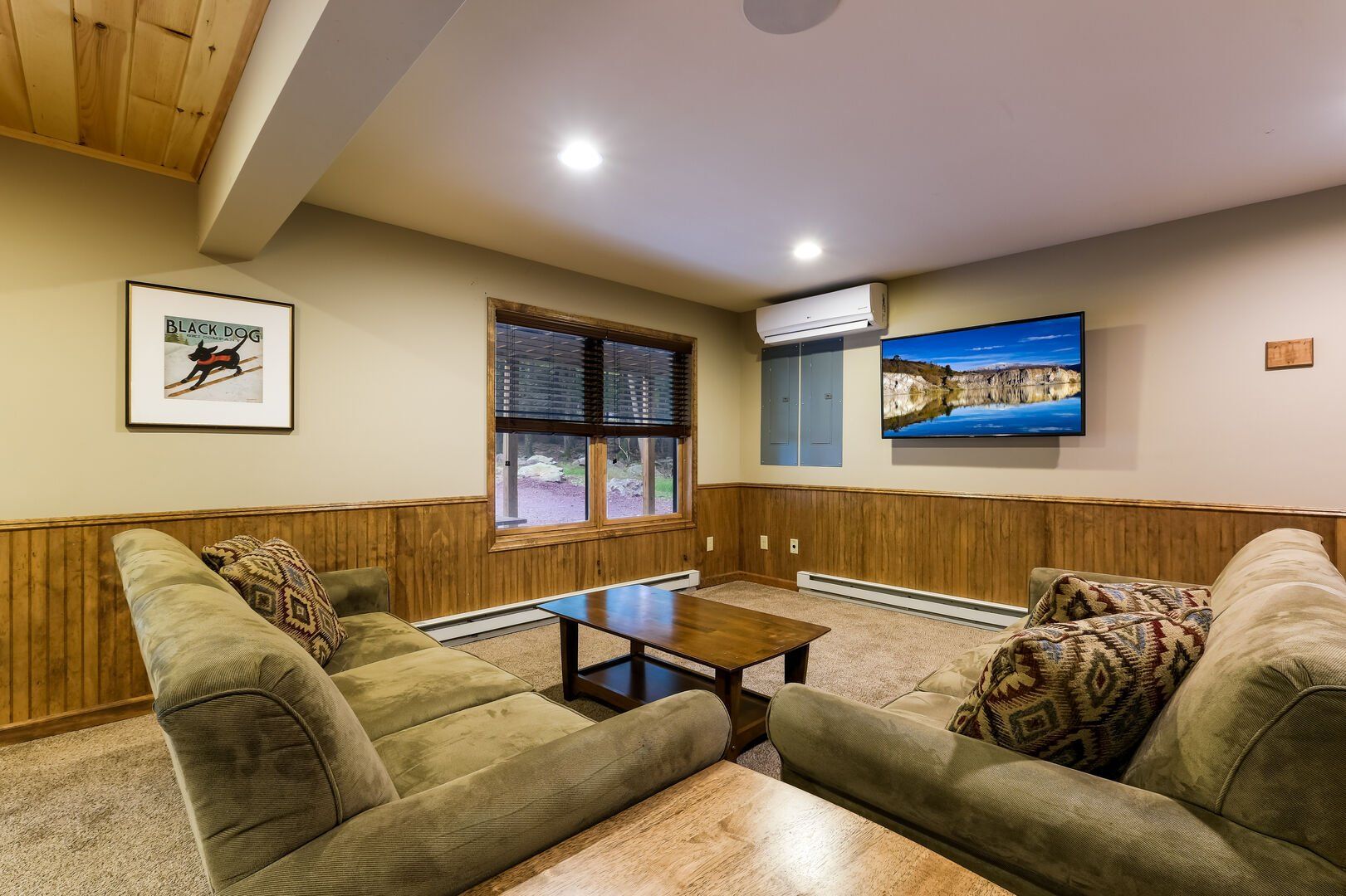 Two couches, coffee table, and TV by the game room.
