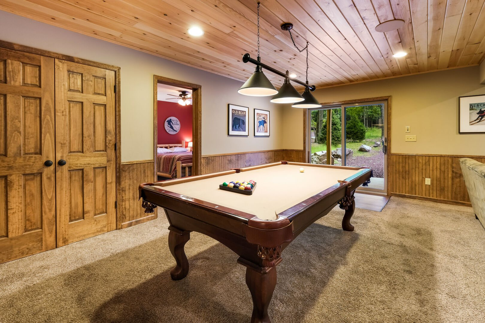 Picture of the pool table in the game room, in front of sliding glass door to backyard.