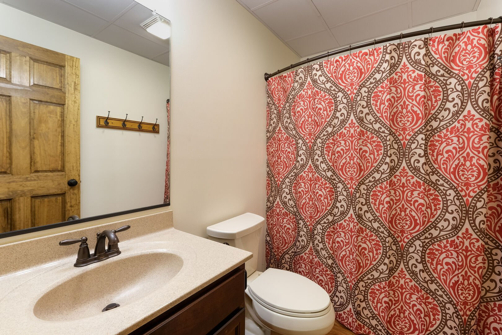 Toilet, sink and mirror, and shower (with curtain closed) of one of this rentals bathroom.