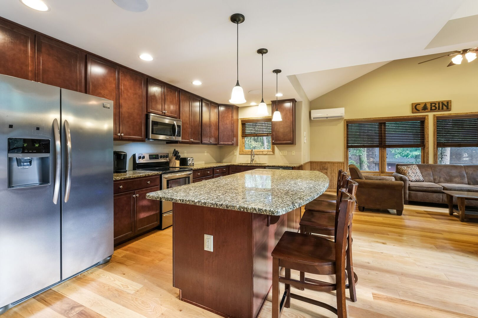 Kitchen island with bar seating, refrigerator, oven, and microwave. Living area seating visible to the right.