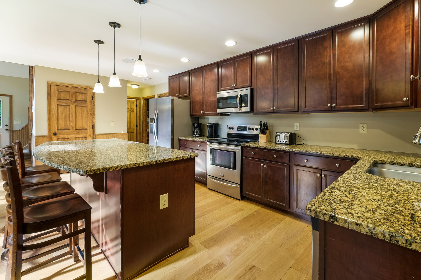 Picture of the kitchen, with center island with chairs, microwave, oven, and refrigerator.