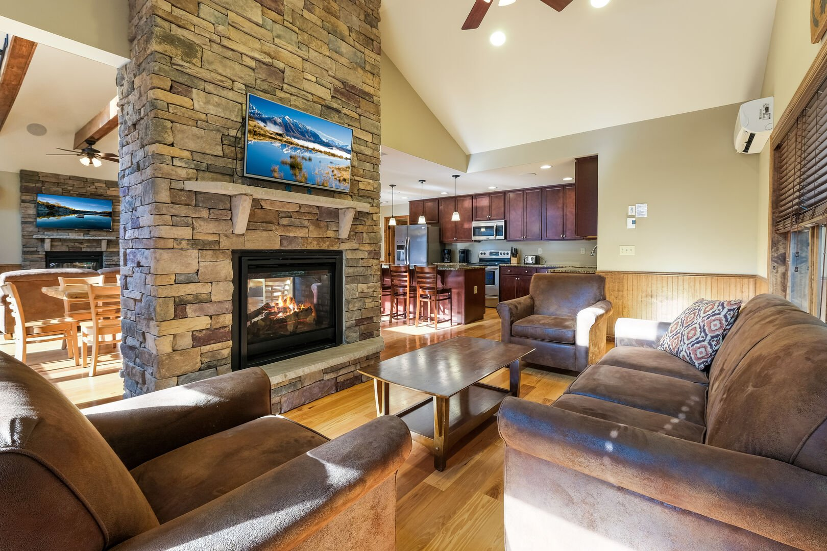 The great room of this luxurious Poconos vacation rental, with couches, coffee table, fireplace, and TV.