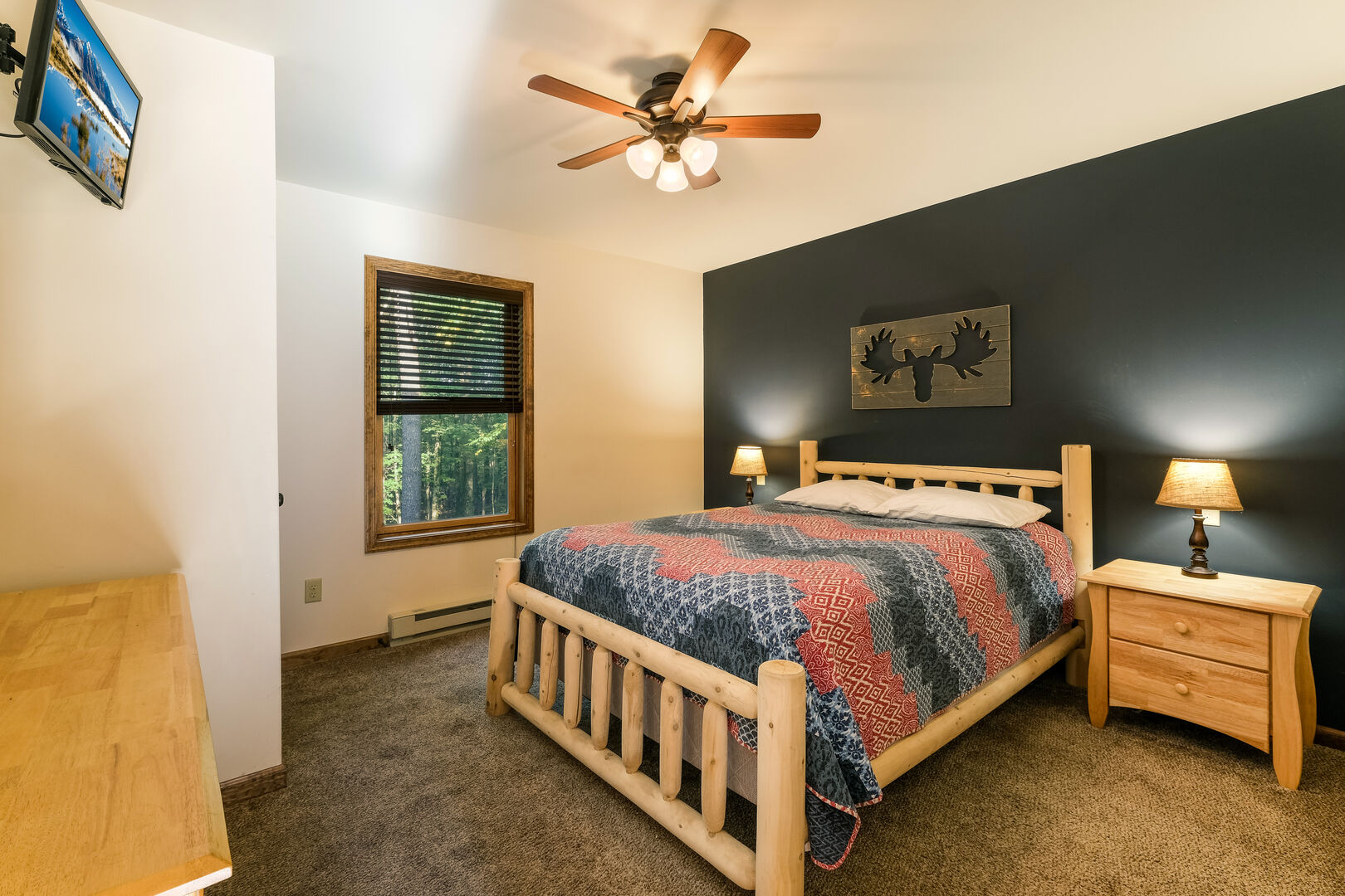 A moose painting hangs over a large bed in the center of the room, with nightstands on either side, and a dresser and TV at the foot of the bed.