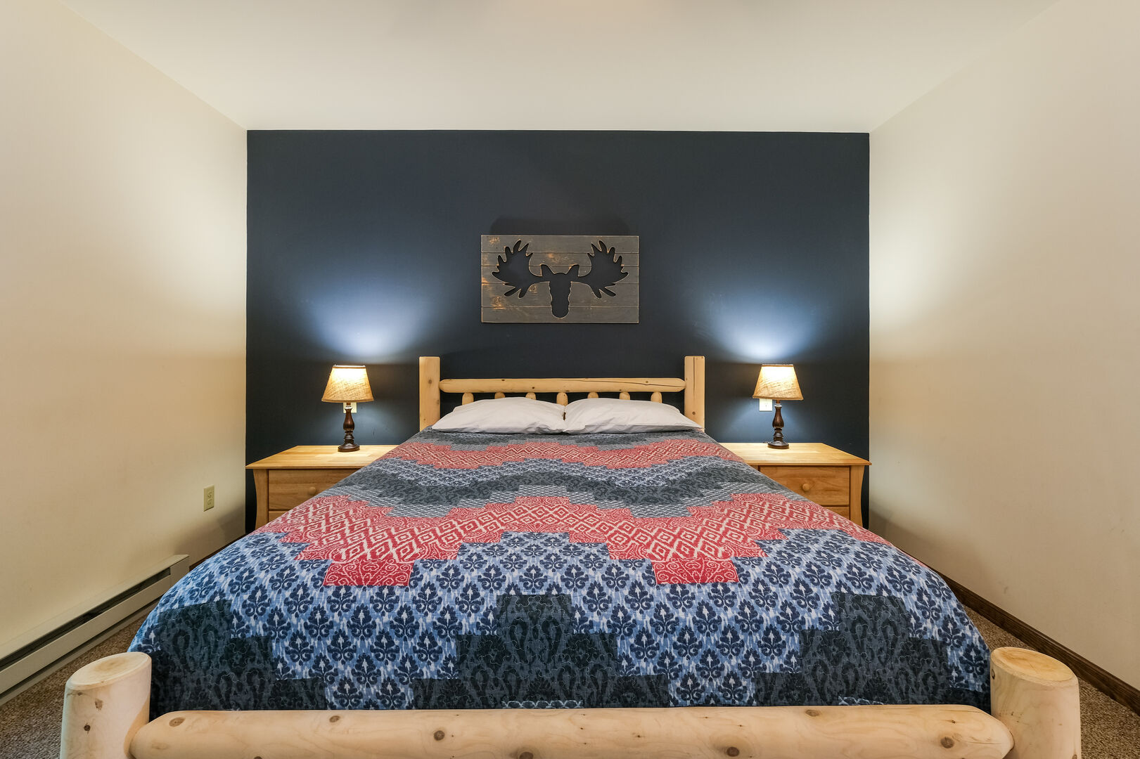 Bed with moose painting over it, nightstands on either side.