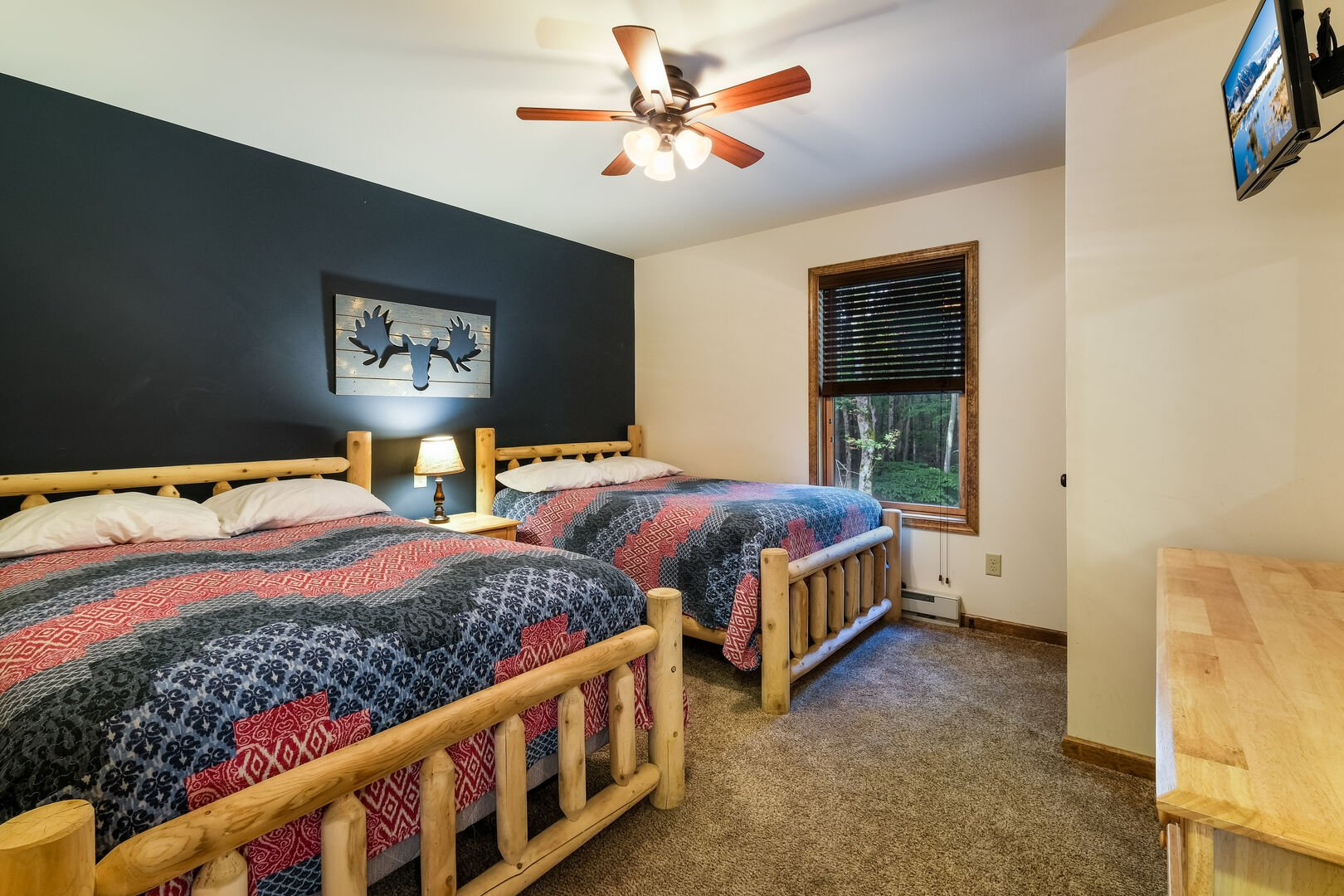 Two side-by-side beds, with a nightstand on either side, and a moose painting over them. Dresser and TV at foot of beds.