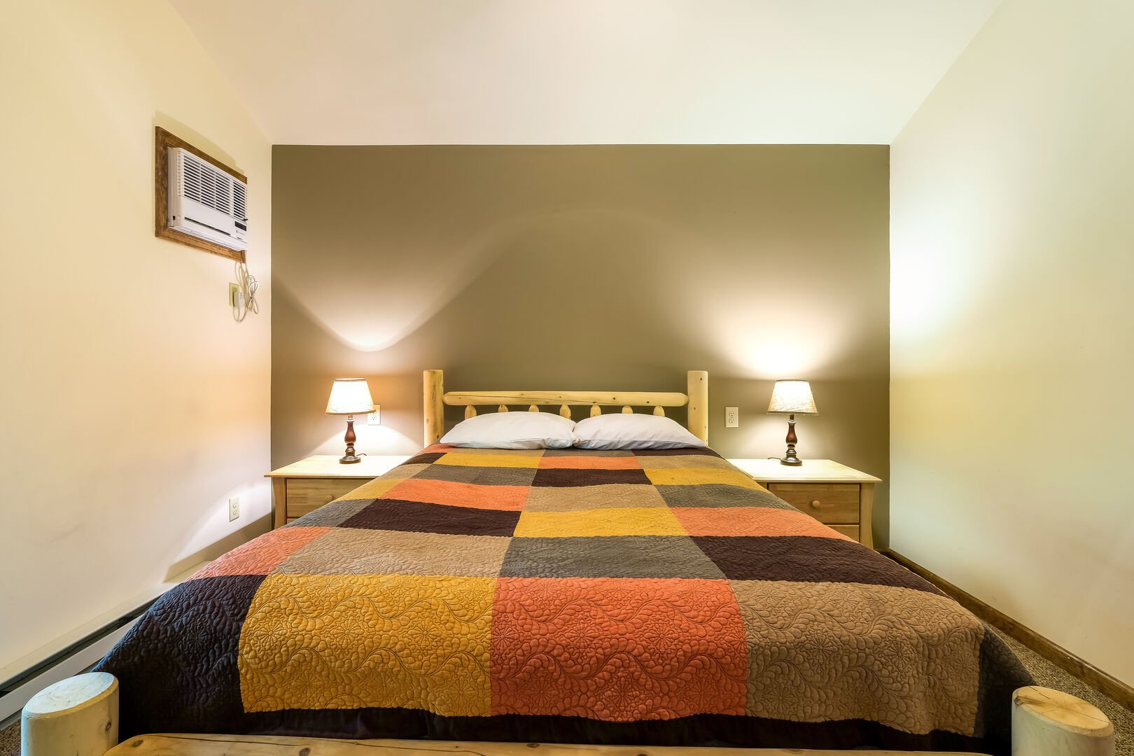 Large bed with two nightstands and lamps on either side. Air conditioner visible to left.