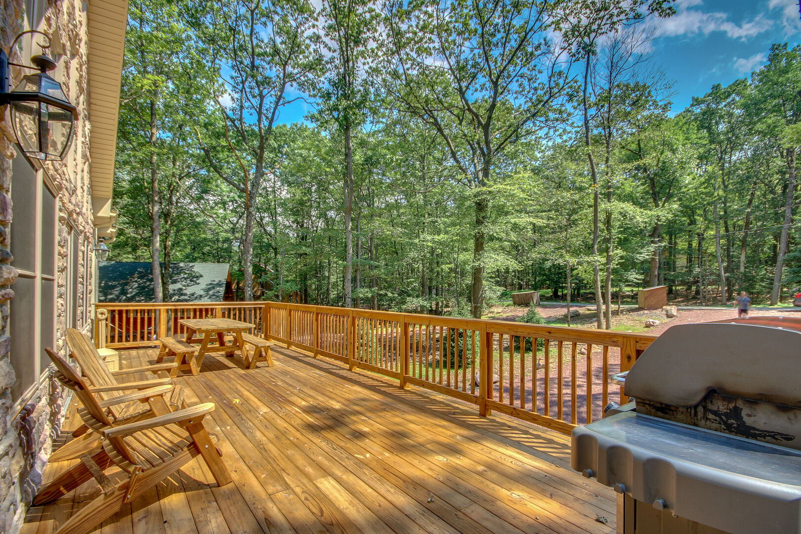 Front porch with picnic table, patio chairs, and grill overlooking  forest scenery.