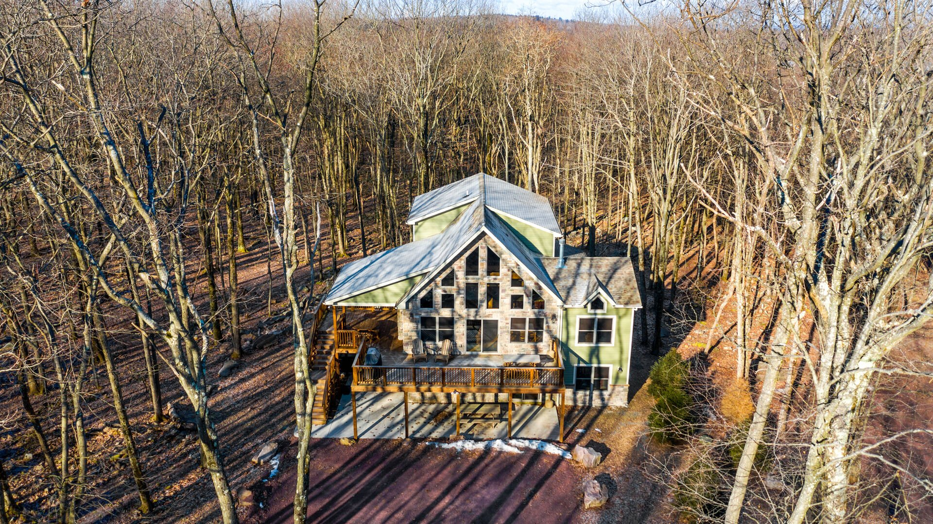 Aerial shot of this luxurious Poconos vacation rental, showing the surrounding forest.