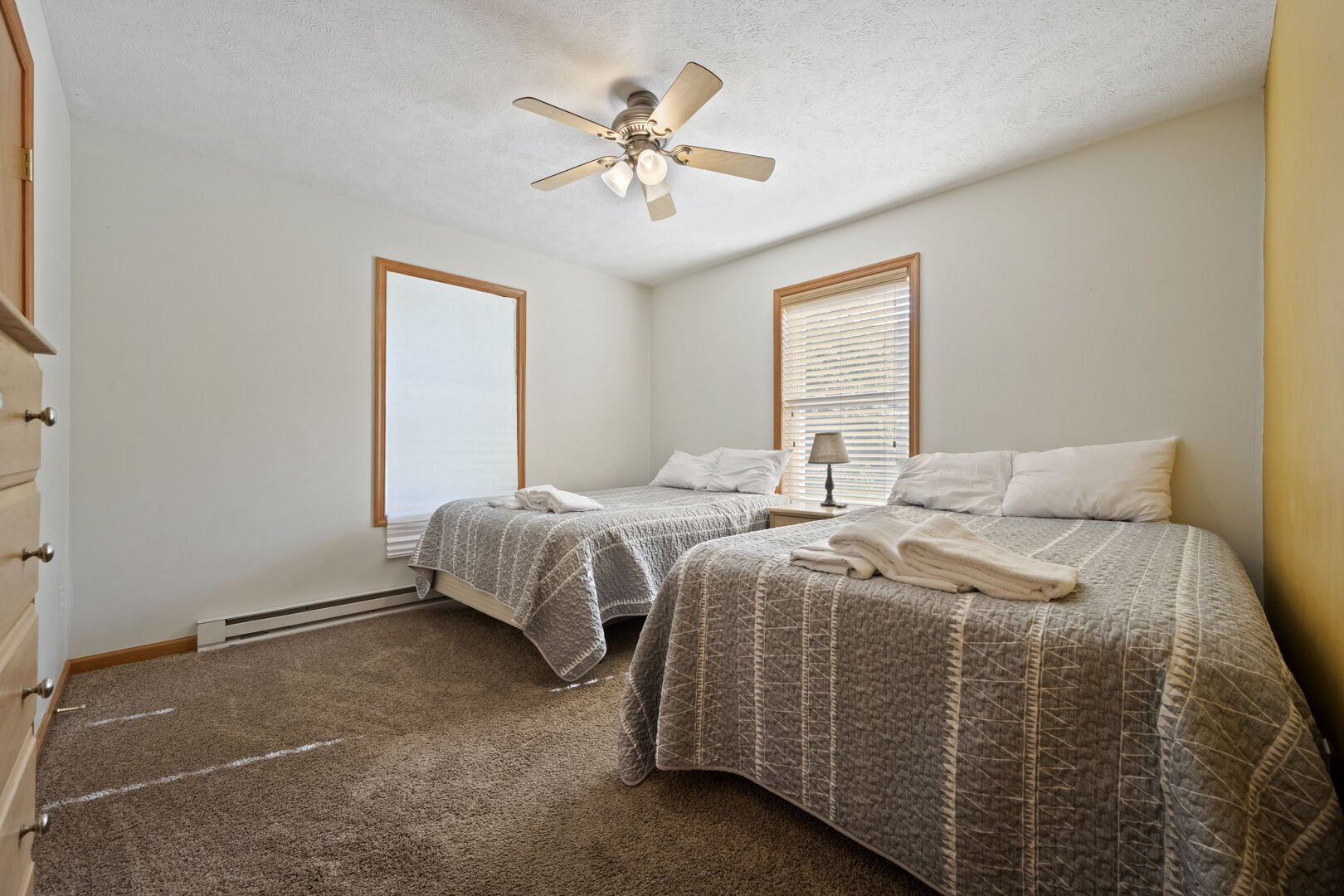 Bedroom with two beds and a ceiling fan.