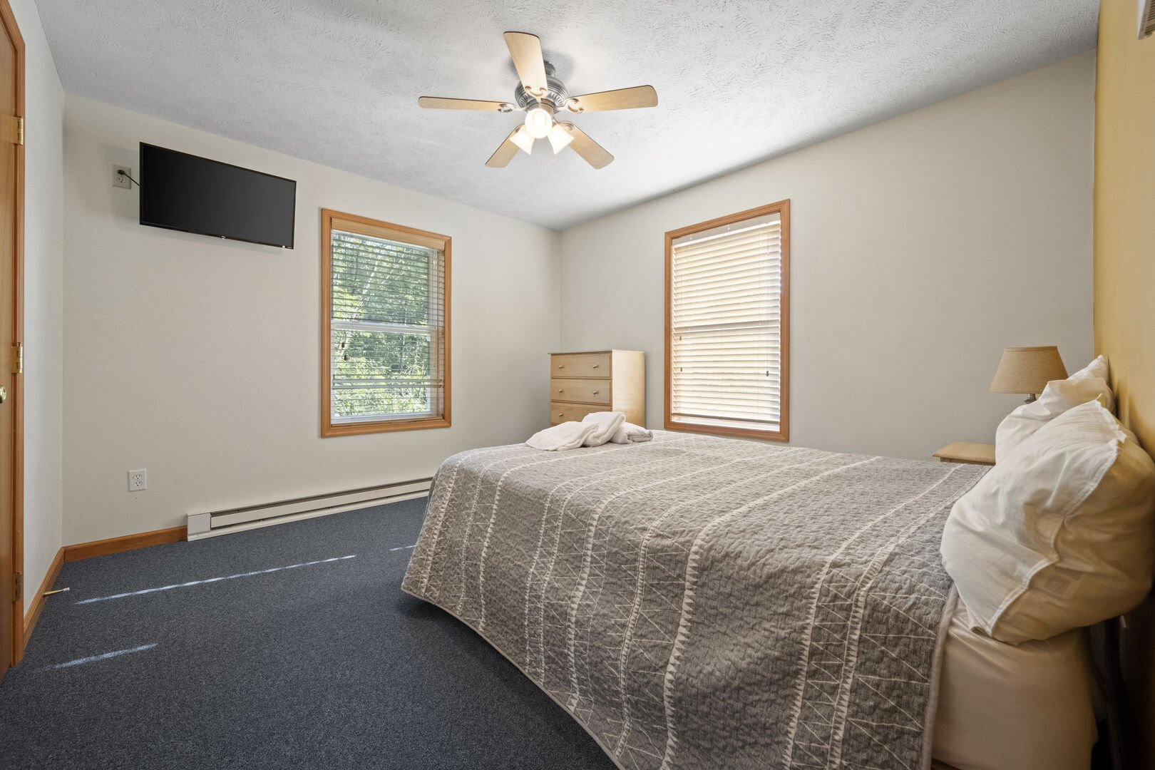 Bedroom with one bed and nearby tv.