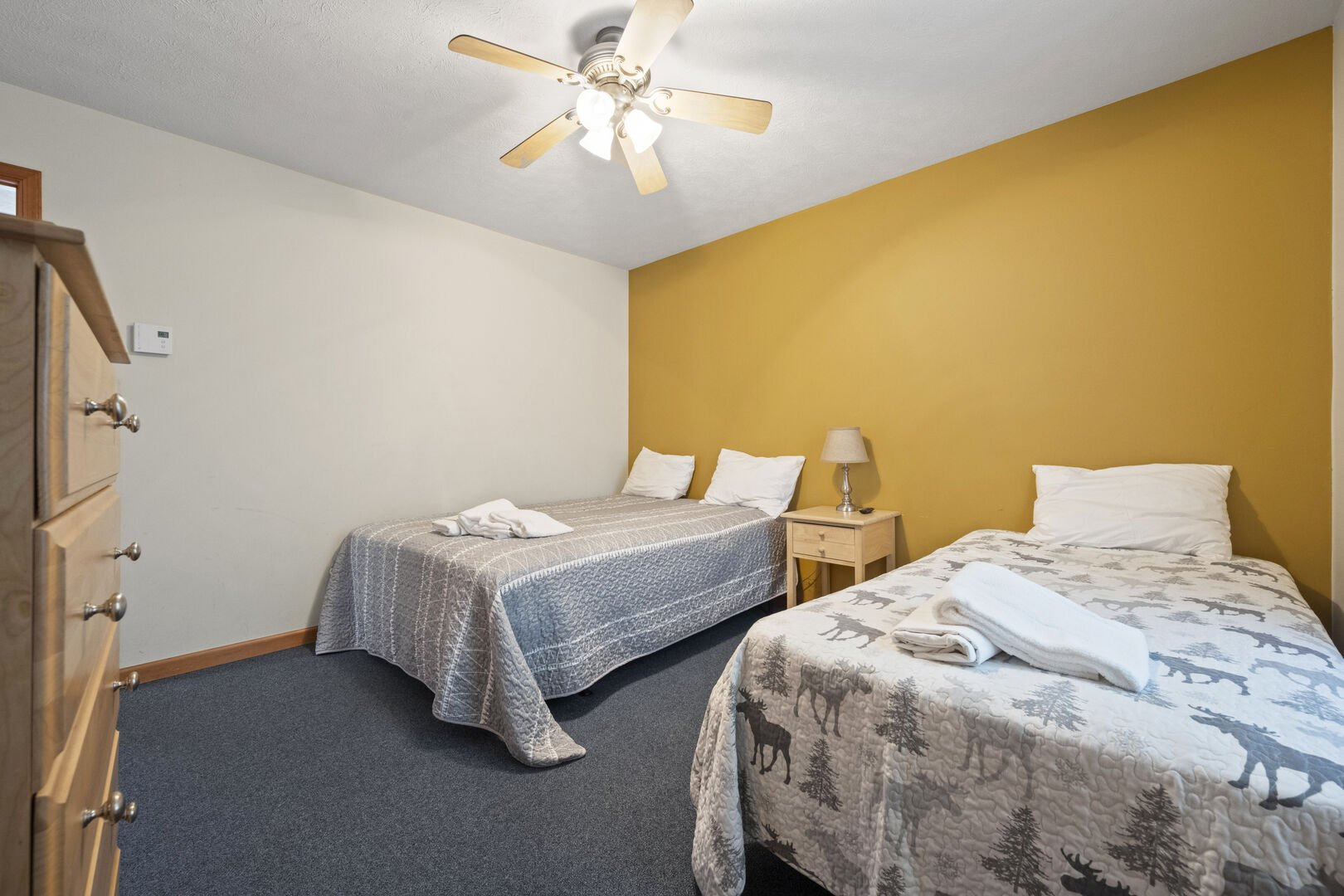 This rental has a bedroom with two beds and a ceiling fan.