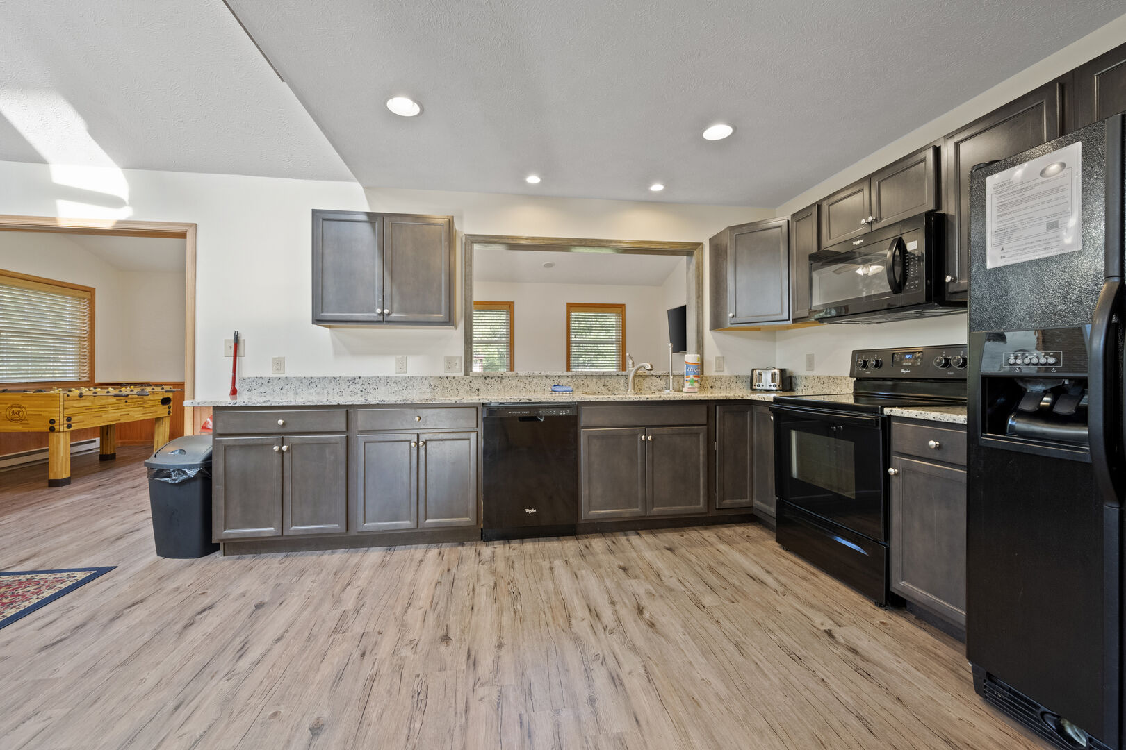 Kitchen area with view of game room.