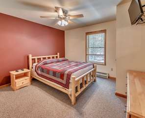 Bedroom with One Bed, Night Stand, and Flat Screen TV in our Poconos Lodge Rental