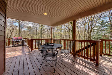 A Table and Three Chairs on Deck of Our Pocono Lakefront Rental.