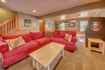 A Large Red Sectional and Coffee Table in Game Room.