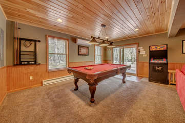 A Spacious Game Room with Pool Table and Arcade Game.