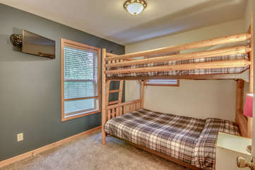 An Image of a Wooden Bunk Bed  and TV on the Wall of Bedroom.