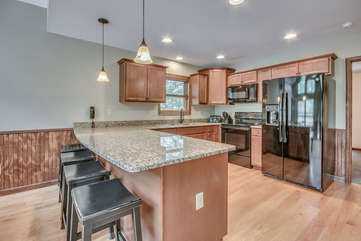 Alternate Angle of On The Rocks Kitchen with Seating, Fridge, and Open Floor Plan