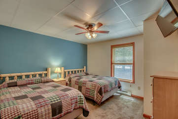 Bedroom with Two Checkered Pattern Beds and Mounted TV