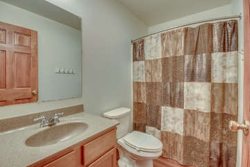 Bathroom with Sink, Toilet and Shower with Brown Patterned Curtain