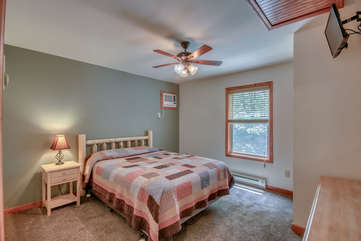 Bedroom with Mounted TV, Nightstand and Bed with Patterned Linens