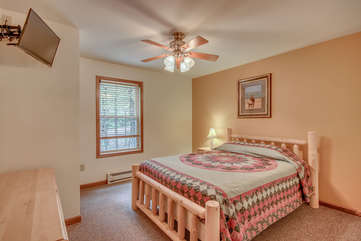 A Large Wooden Bed Facing TV and Dresser.