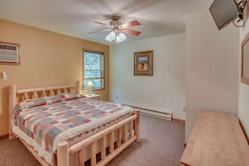 A Large Bed Facing Direction of Wall with TV and Dresser.