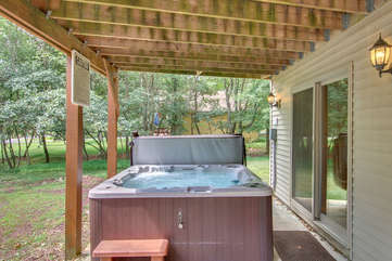 A picture of the outdoor hot tub, powered on with water in it, on the back porch.