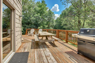 A picture of the upper balcony of this Pocono rental in Towamensing Trails, with its picnic table, grill, and lawn chairs.