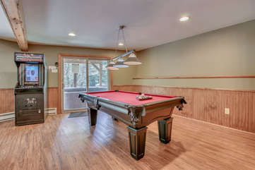 The game room, with a pool table in the center of the room, and an arcade cabinet near the back sliding glass door.