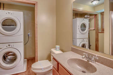 Bathroom with a sink and mirror, toilet, washer and dryer.