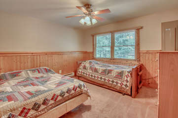 One of the bedrooms in this Pocono rental in Towanensing Trails, with a bed and couch against the wall.