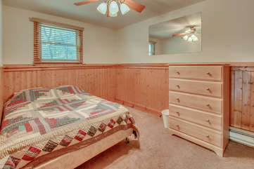 Picture of a bedroom with a quilt covered bed, dresser, and mirror on the wall.