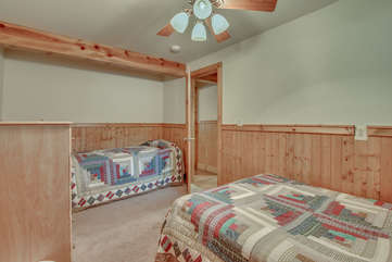 A quilt covered bed, couch, and the ceiling fan in one of this homes bedrooms.