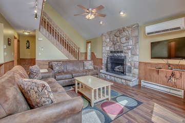 The great room of this Pocono rental in Towamensing Trails, with two couches, a fireplace, a coffee table, and TV.
