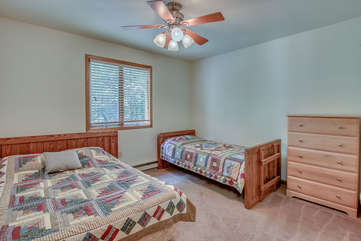 A bedroom with a bed on the left wall, a smaller bed and dresser on another.