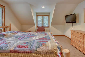 The master bedroom of this Pocono rental in Towamensing Trails, with bed, dresser, armchair, and TV.