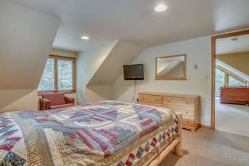 Another shot of the master bedroom of this Pocono rental in Towanmensing Trails, with a bed, armchair, dresser, TV and Mirror in shot. The door opens to upper floor.