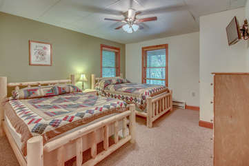 Bedroom with Two Beds, Nightstand, Dresser, Ceiling Fan, and TV.